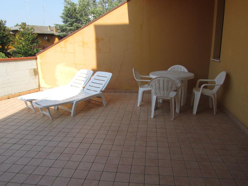 Лежаки и столик на террасе в квартире у моря в Лидо делле Национи, Эмилья-Романия, Италия.