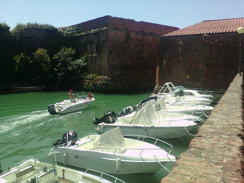 По узкому проходу яхты проплывают мимо замка к морю