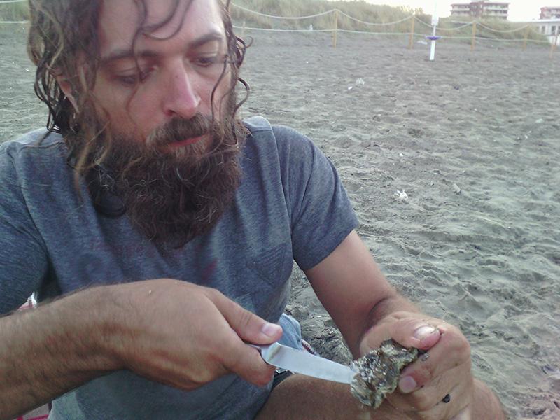 Муж специальным ножом открывает устрицы на пляже
